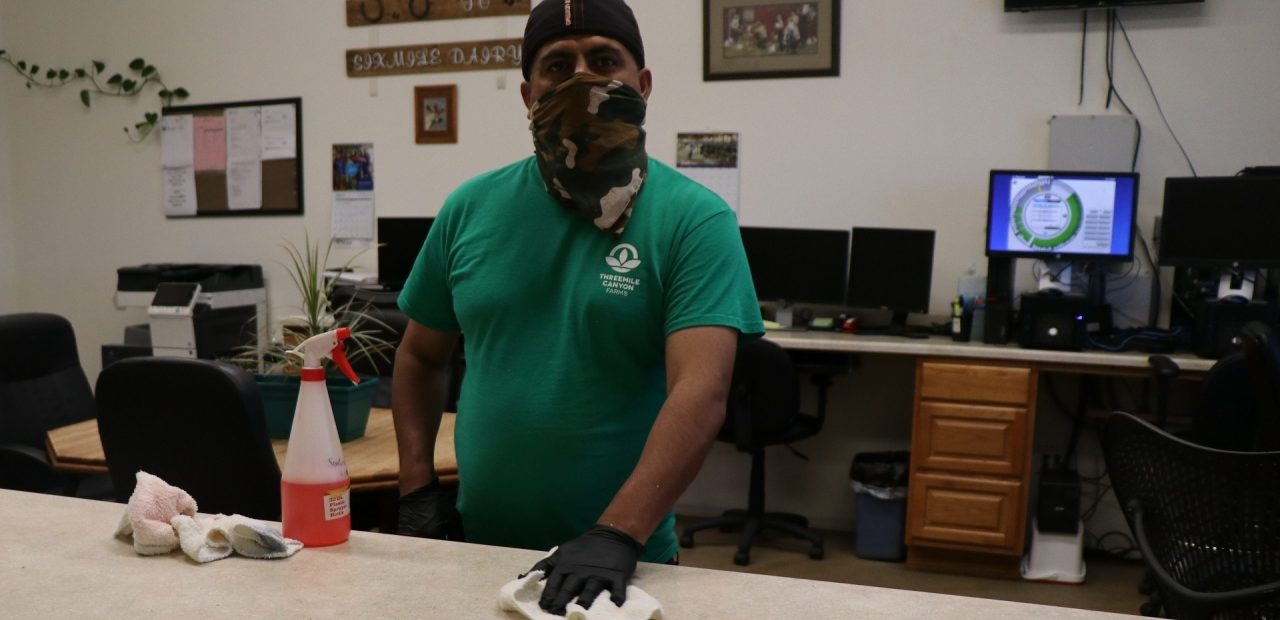 man in mask cleaning in office